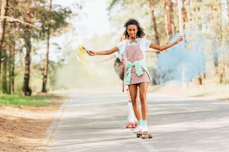 Full length view of two girls skateboarding with blue and yellow smoke grenade on road