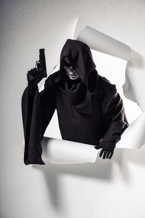 Woman in death costume holding gun and getting out of hole in paper