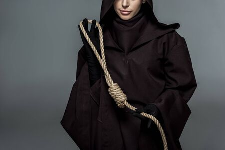 Cropped view of woman in death costume holding hanging noose isolated on grey background