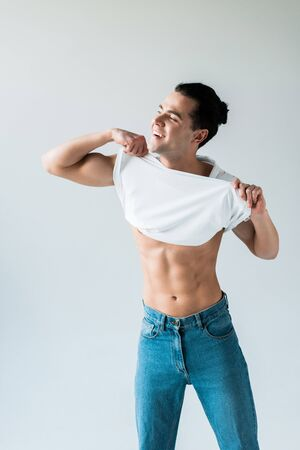 Happy man taking off white t-shirt and smiling on white background