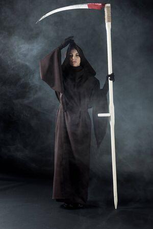 Ganzkörperansicht einer Frau im Todeskostüm mit Sense auf schwarzem Hintergrund mit Rauch with Standard-Bild