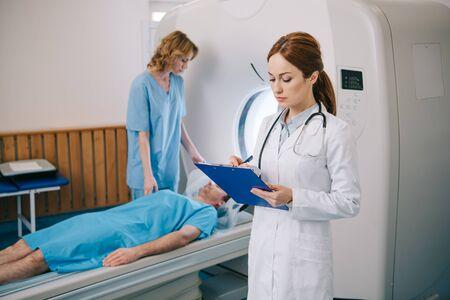 Nurse preparing patient for mri scanning while radiologist writing on clipboard Zdjęcie Seryjne