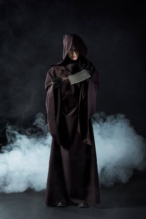 Full length view of woman in death costume holding cleaver in smoke on black background
