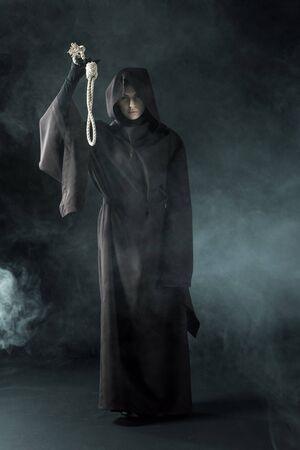 Full length view of woman in death costume holding hanging noose in smoke on black background