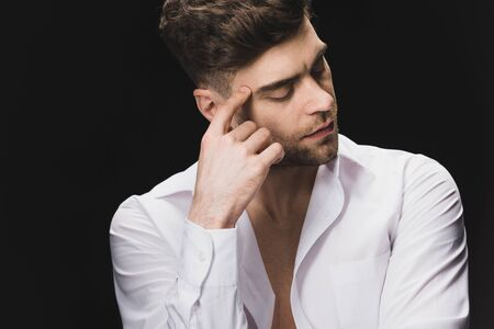 serious handsome man in white shirt holding hand near face isolated on black Stock Photo