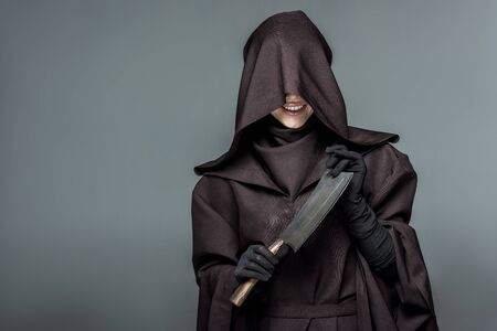 Smiling woman in death costume holding cleaver isolated on grey background