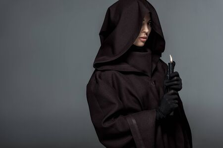 Woman in death costume holding burning candle isolated on grey background