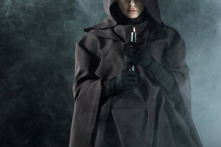 Partial view of woman in death costume holding candle in smoke on black background