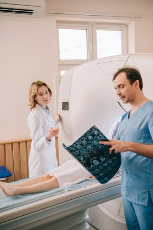 Doctor looking at tomography diagnosis while radiologist operating ct scanner during patients diagnostics