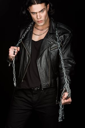 Handsome man looking at camera while holding chains isolated on black background