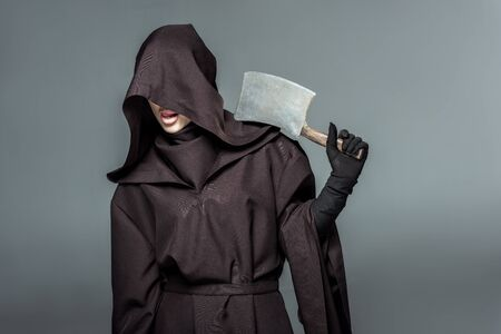 Woman in death costume holding cleaver isolated on grey background Banco de Imagens - 125073672