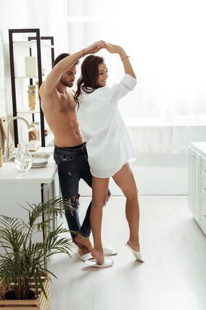 handsome shirtless man dancing with happy girl in kitchen