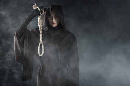 Front view of woman in death costume holding hanging noose in smoke on black background