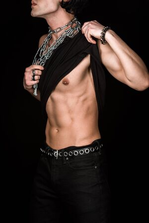 Cropped view of muscular man touching tank top and chains while standing isolated on black background Stock Photo
