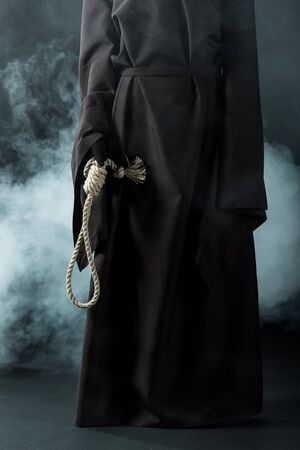 Cropped view of woman in death costume holding hanging noose on black background