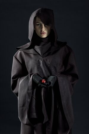 Woman in death costume holding dice isolated on black background