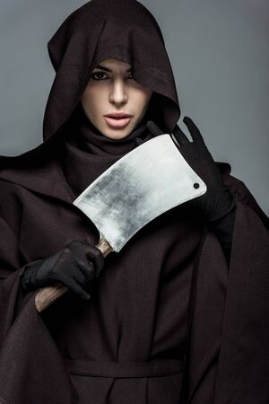 Woman in death costume holding cleaver isolated on grey background