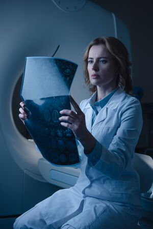 Serious doctor looking at x-ray diagnosis while sitting near ct scanner Zdjęcie Seryjne