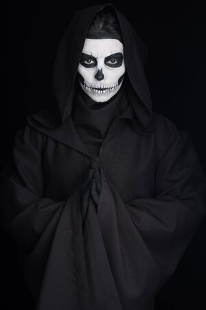 Woman with skull makeup showing please gesture isolated on black background 版權商用圖片