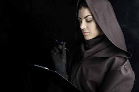 Woman in death costume holding clipboard on black background