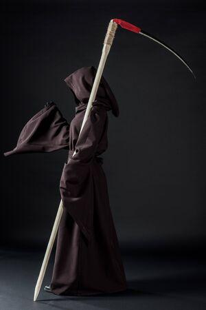 Seitenansicht einer Frau im Todeskostüm mit Sense auf schwarzem Hintergrund