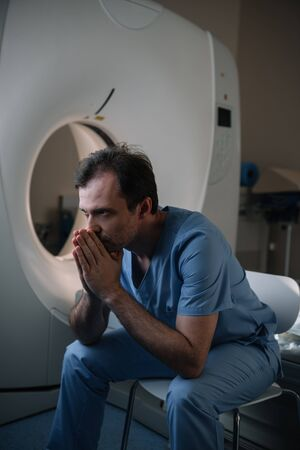 Thoughtful radiologist sitting near computed tomography scanner in hospital and looking away Zdjęcie Seryjne