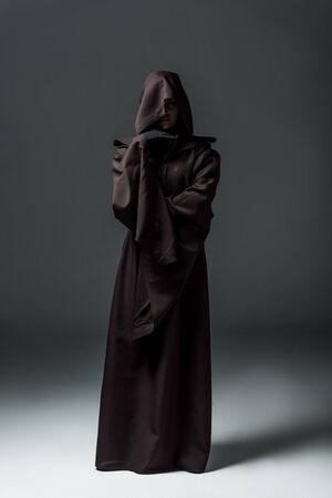 Full length view of woman in death costume on grey background