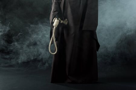 Partial view of woman in death costume holding hanging noose in smoke on black background