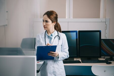 Selective focus of attentive doctor writing on clipboard and looking away
