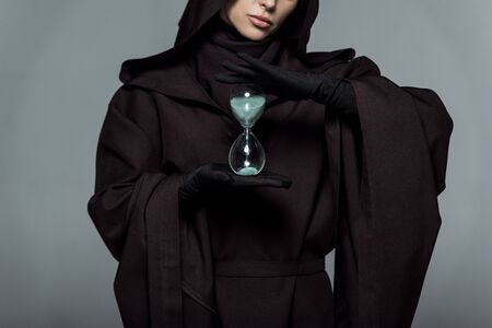 Partial view of woman in death costume holding sand clock isolated on grey background