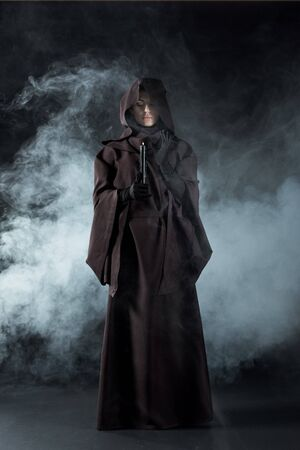 Full length view of woman in death costume holding candle in smoke on black background Imagens