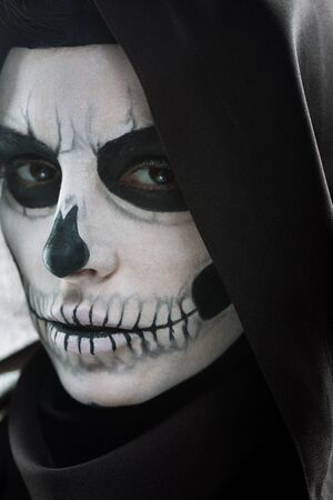 Serious woman in black hood with skull makeup looking at camera