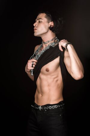 Muscular man touching tank top and chains while standing isolated on black background Stock Photo
