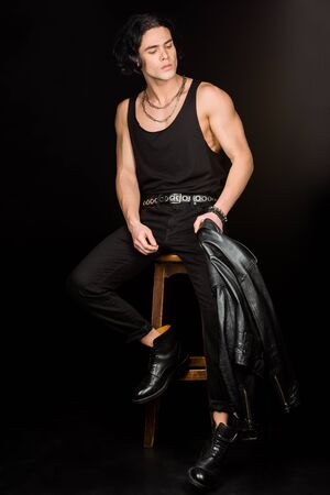 Handsome man holding leather jacket and sitting on wooden chair on black background