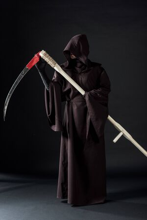 full length view of woman in death costume holding scythe on black Фото со стока