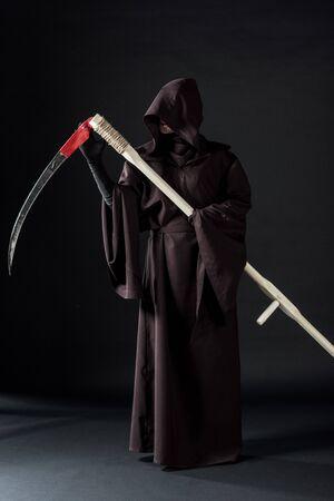 Ganzkörperansicht einer Frau im Todeskostüm mit Sense auf schwarzem Hintergrund
