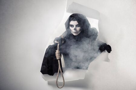 Woman in death costume holding hanging noose and getting out of hole in paper