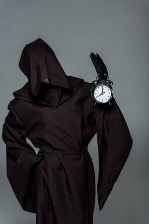 Woman in death costume holding alarm clock isolated on grey background Banco de Imagens - 125074060