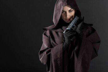Woman in death costume holding gun isolated on black background