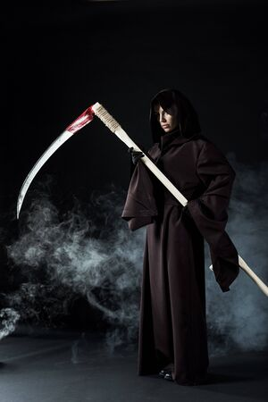 Ganzkörperansicht einer Frau im Todeskostüm mit Sense auf schwarzem Hintergrund mit Rauch with