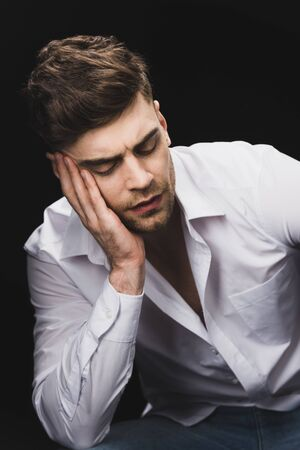 pensive handsome man in white shirt holding hand near face isolated on black