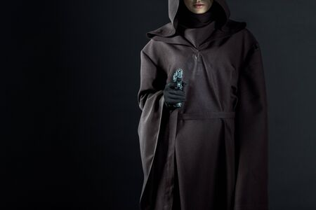 Cropped view of woman in death costume aiming gun at camera on black background
