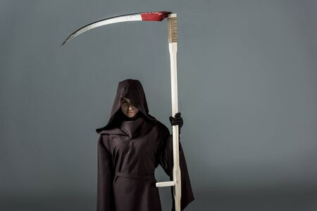 Woman in death costume holding scythe on grey background Imagens
