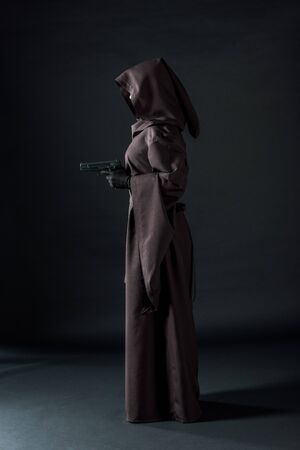 Side view of woman in death costume holding gun on black background
