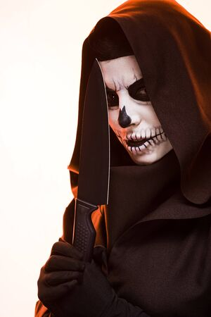 Woman with skull makeup holding knife isolated on white background Imagens