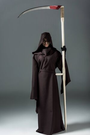 Full length view of woman in death costume holding scythe on grey background
