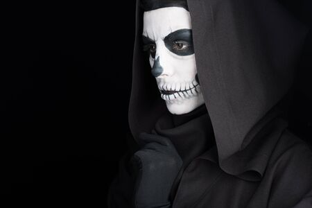 Woman with skull makeup looking away isolated on black background