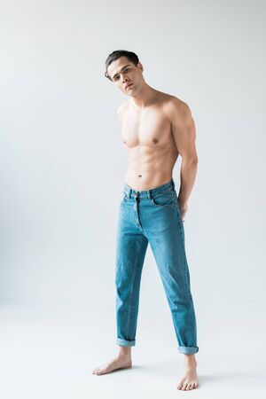 handsome shirtless man standing in blue jeans and looking at camera on white