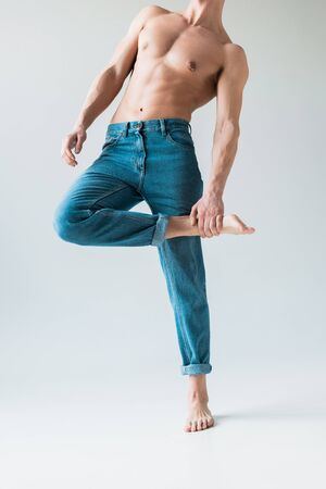 cropped view of shirtless man with touching leg while standing in blue jeans on white