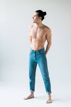 handsome shirtless man standing in blue jeans on white Banco de Imagens
